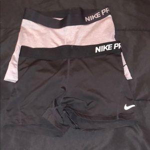 2 nike pro shorts, one black one grey